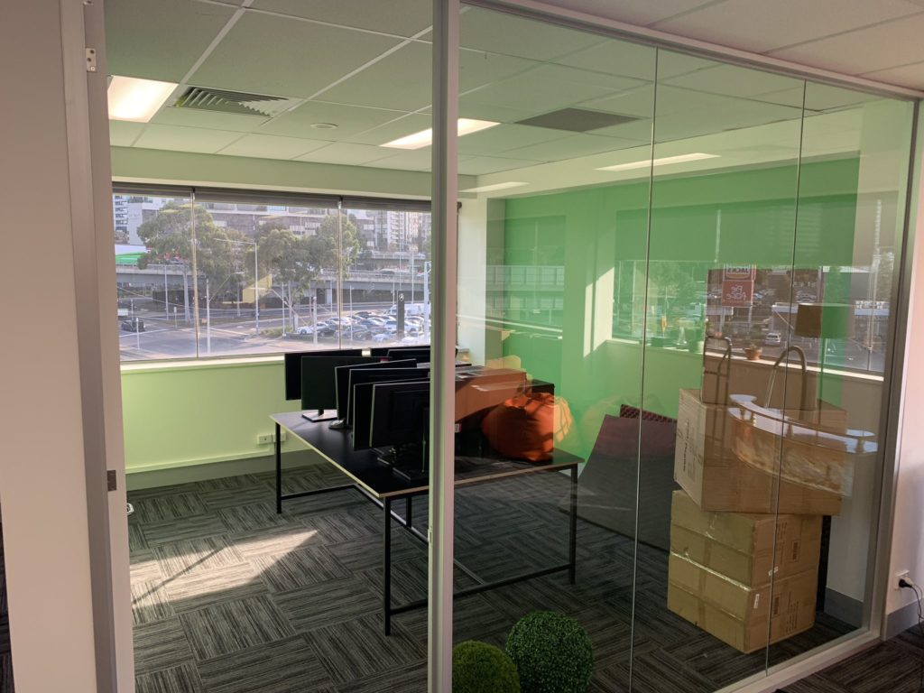 A small office with glass doors and computers inside that is being set up as the streaming room