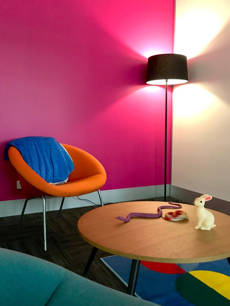 A breakout area of the office with a pink wall, orange chair, and a coffee table topped with a toy rabbit and snakes