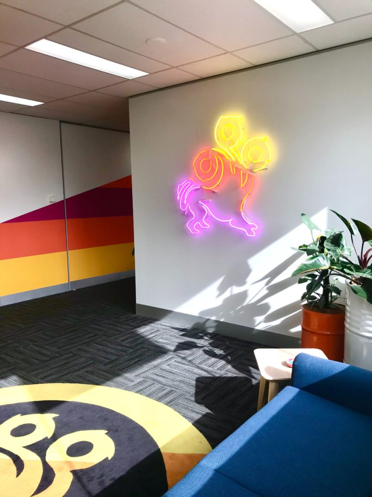 An office wall featuring a neon sign version of the League of Geeks logo
