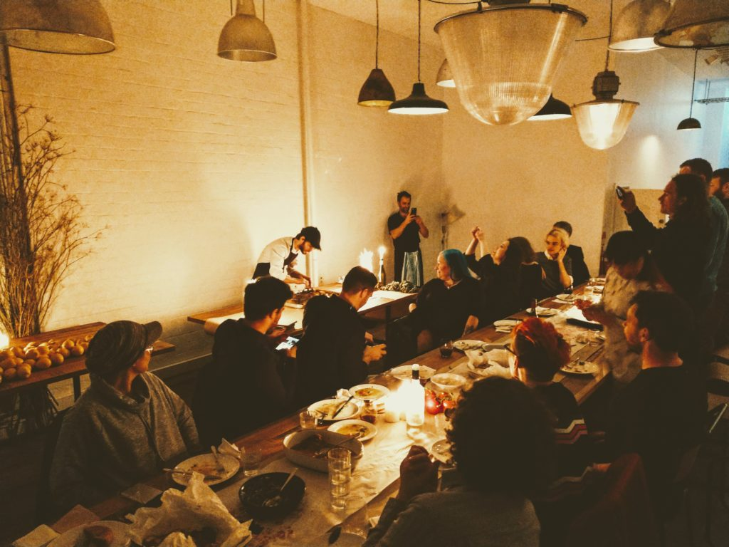 A group of people sat at long wooden table taking photos of a chef preparing food behind them